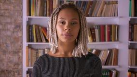 Ung afrikansk flicka med dreadlocks som bort ser, tänker och ler Bokhyllor i bakgrunden stock video