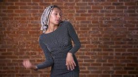 Ung afrikansk flicka med dreadlocks som dansar och ser kameran, tegelstenvägg i bakgrunden arkivfilmer