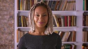 Ung afrikansk flicka med dreadlocks som ler, skrattar och ser kameran, bokhyllor i bakgrunden arkivfilmer