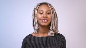 Ung afrikansk flicka med dreadlocks som ler, skrattar och ser kameran, vit bakgrund lager videofilmer