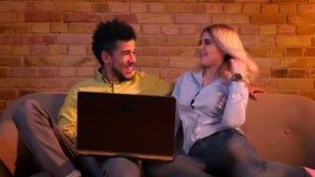 Ung afrikansk grabb och caucasian flicka som sitter på soffan och håller ögonen på in i bärbara datorn som den är glad och koppla lager videofilmer