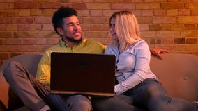 Ung afrikansk grabb och caucasian flicka som sitter på soffan med bärbara datorn och kramar vara glat och kopplat av hemma lager videofilmer