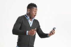 Ung afrikansk grabb som ser mobiltelefonen Fotografering för Bildbyråer