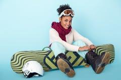 Ung afrikansk kvinna på blå förberedelse för begrepp för snowboarding för sport för väggstudiovinter royaltyfri fotografi