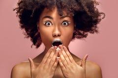 Ung afrikansk kvinna på chockad stilfull makeup för rosa väggstudiomode arkivbild