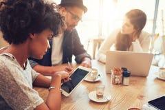 Ung afrikansk kvinna som använder den digitala minnestavlan med vänner på kafét Royaltyfri Bild