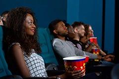Ung afrikansk kvinna som håller ögonen på en film Royaltyfri Foto