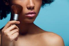 Ung afrikansk kvinna som isoleras på blå borste för innehav för photoshoot för väggstudiomode royaltyfri bild