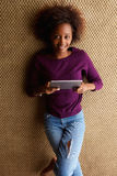 Ung afrikansk kvinna som ner ligger med den digitala minnestavlan Arkivbilder
