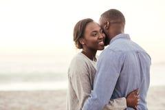 Ung afrikansk kvinna som omfamnar hennes make på stranden arkivfoto