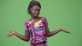 Ung afrikansk kvinna som rycker på axlarna skuldror stock video