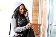 Ung afrikansk kvinna som talar på en mobiltelefon arkivbild