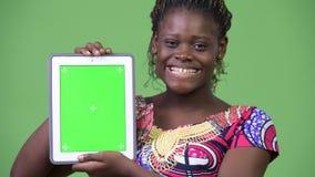 Ung afrikansk kvinna som visar den digitala minnestavlan arkivfilmer