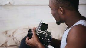 Ung afrikansk man i pyjamas som sitter på den gamla photocameraen för säng och för innehav Talande foto för grabb på flyttning-fi lager videofilmer