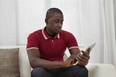 Ung afrikansk man som använder den Digital minnestavlan arkivfoto