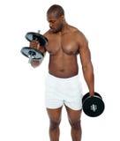 Ung afrikansk man som gör bicepsövning Fotografering för Bildbyråer