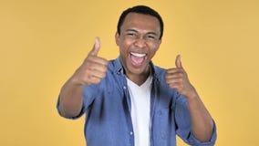 Ung afrikansk man som gör en gest upp tummar, gul bakgrund arkivfilmer