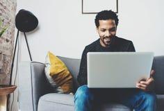 Ung afrikansk man som ler och använder bärbara datorn, medan sitta på hans moderna hem- studio Begrepp av lyckligt arbeta för fol Arkivfoto