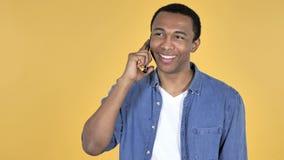Ung afrikansk man som talar på Smartphone, gul bakgrund lager videofilmer