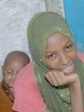 Ung afro- skönhet som bär sova, behandla som ett barn flickan på henne tillbaka Royaltyfri Foto