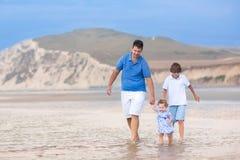 Ung aktiv fader på den härliga stranden med hans ungar Arkivfoto