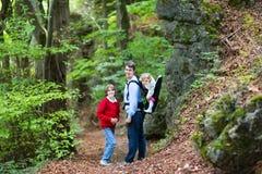 Ung aktiv fader som fotvandrar i klippa och skog med ungar Royaltyfri Fotografi