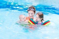Ung aktiv moder i simbassäng med två ungar Royaltyfri Foto