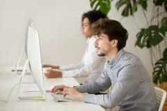 Ung allvarlig anställd fokuserade på datorarbete i blandras- nolla arkivfoto