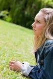 Ung allvarlig kvinna som ser framåt stunder som ligger på gräset Royaltyfria Foton