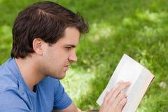 Ung allvarlig man som läser en bok Arkivfoto