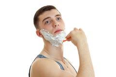 Ung allvarlig man som rakar hans skägg och åt sidan ser Arkivbild
