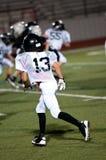 Ung amerikansk fotbollsspelare på försvar. Arkivfoton