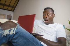 Ung amerikansk man för upphetsad och förvånad ung svart afro i nätverkande för misstro- och chockframsidauttryck med bärbar dator royaltyfri bild