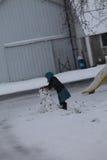 Ung Amish flicka som bygger en snögubbe Arkivbilder