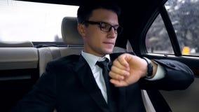 Ung angelägen affärsman som är sen för flyg och att se klockan, trafik i stad royaltyfri bild