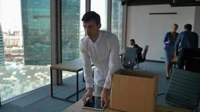 Ung anställd packar upp asken med docs och objekt Hans kollegor går nära i modernt kontor stock video