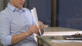 Ung anställd som förhalar med den pappers- nivån på arbetsplats och att ha gyckel arkivfilmer
