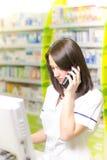 Ung apotekarekvinna som uttrycker under, medan ha en påringning farmaceutisk bakgrund apotek Preventivpillerar och medicin Royaltyfri Bild