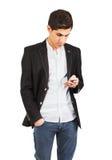 Ung arab i det svarta omslaget med en telefon i handen Arkivbild