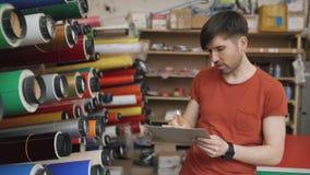 Ung arbetare i lager med skrivplattan som kontrollerar inventarium Mannen arbetar i försäljningsavdelning av advertizingmaterial arkivfilmer