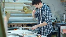 Ung arbetare som klipper exponeringsglaset för ram i ramseminarium som klipper plötsligt hans finger Royaltyfri Fotografi