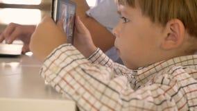 Ung arbetefader som talar på telefonen, hans hållande ögonen på video för liten son på minnestavlan, upptaget och koncentrerat stock video