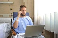 Ung arbetsnarkomanaffärsman i sjukhusrum som är sjukt och som är sårat efter olyckan som arbetar med mobiltelefon- och datorbärba arkivbilder