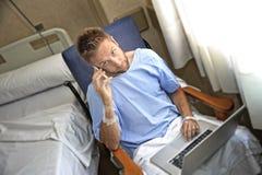 Ung arbetsnarkomanaffärsman i sjukhusrum som är sjukt och som är sårat efter olyckan som arbetar med mobiltelefon- och datorbärba fotografering för bildbyråer