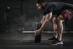 Ung arg färdig idrottsman nen som förbereder skivstången för lyftande vikt på idrottshallen Skivstångmagnesiaskydd Stilig man som royaltyfria foton