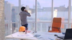 Ung arkitekt som arbetar med ritningar i kontoret lager videofilmer