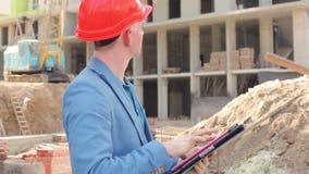 Ung arkitekt som arbetar på en minnestavla nära konstruktionsplatsen stock video