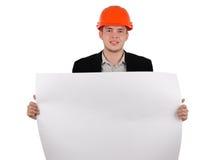 Ung arkitekt som rymmer ett byggnadsplan Arkivfoto