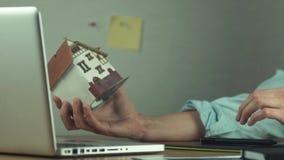 Ung arkitekt som skapar byggprojekt på modell för bärbar datorinnehavhus i hand lager videofilmer