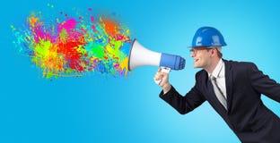 Ung arkitekt som skriker med megafonen och färgrikt färgstänkbegrepp fotografering för bildbyråer